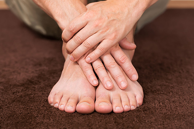 Male hands crossed over healthy resting feet.
